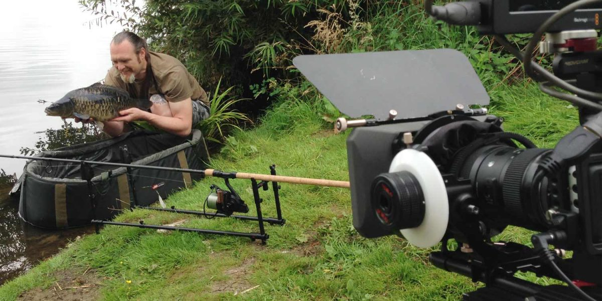 A man crouches by a lake holding a carp with a rod underneath him, whilst a video production camera is in the foreground