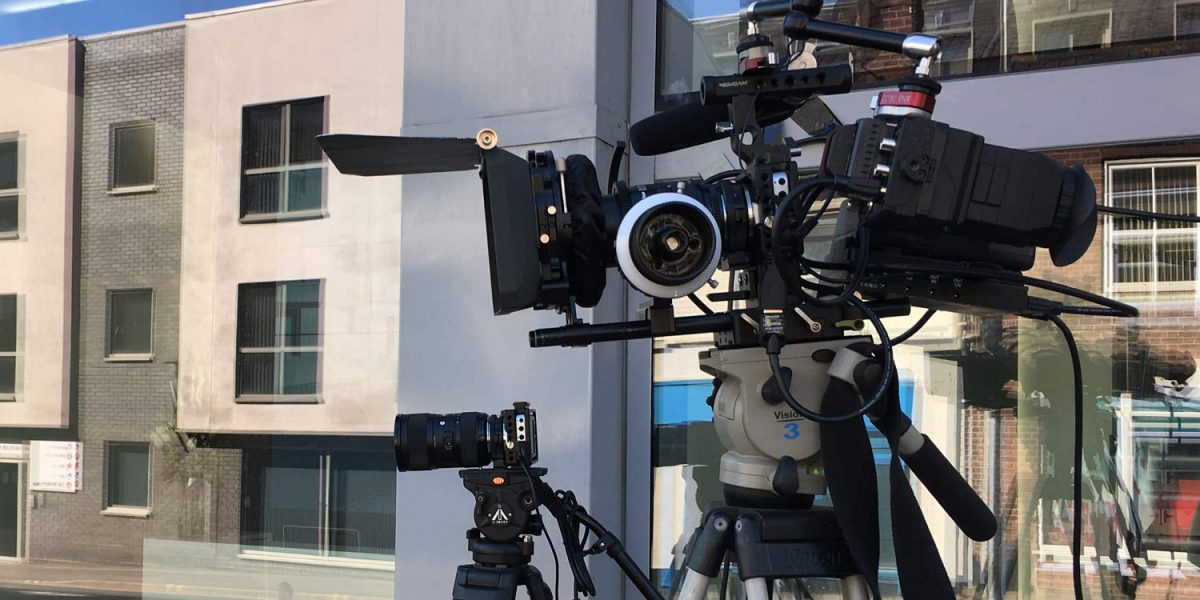 Two professional video cameras sit on tripods outside an office building