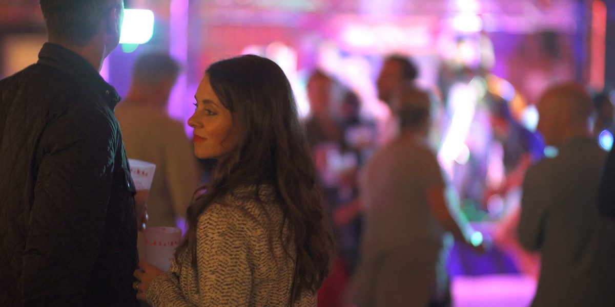 Porkstock 2017 the movie, a girl stands looking away from a busy dancefloor with a band in the background