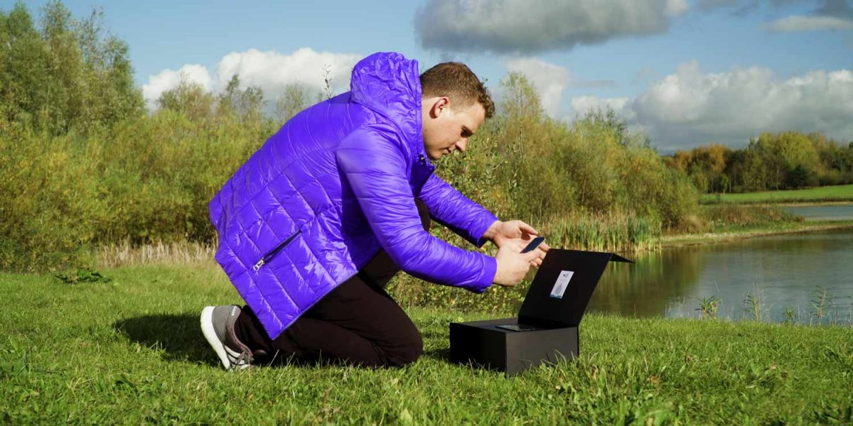 In a corporate video production, a man kneels by a box by a lake scanning a label inside the box with a smartphone