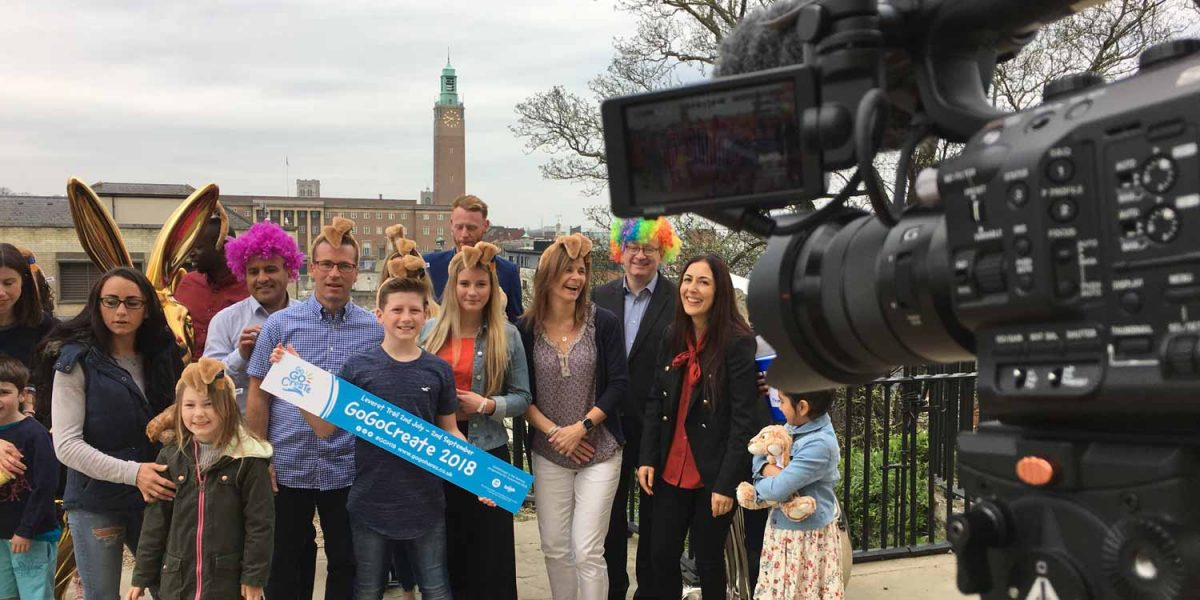 A group of people stand in front a of a TV camera in Norwich city centre