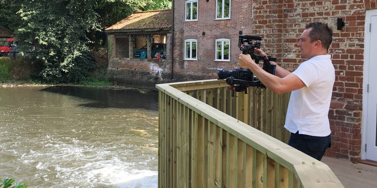 A cameraman stands over a mill house pool with a camera on a handheld gimbal stabilizer
