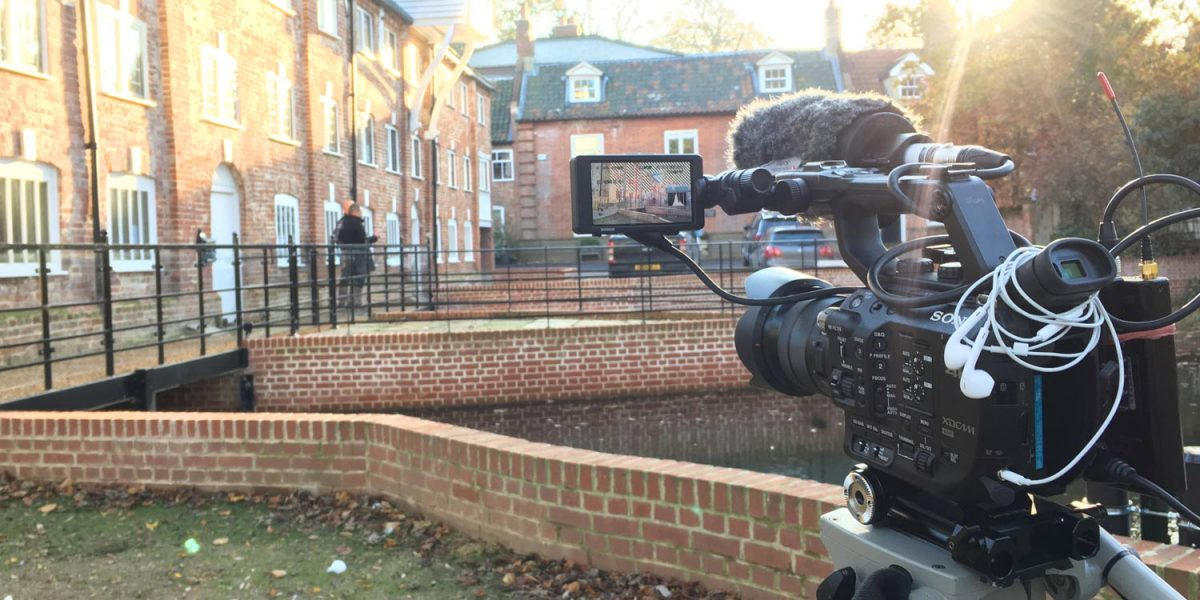 A broadcast quality camera films outside an expensive house for an estate agent