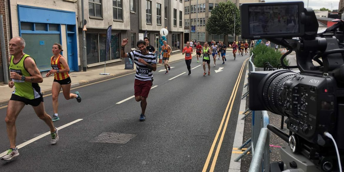 A video camera looks on as runners competing in Run Norwich go past